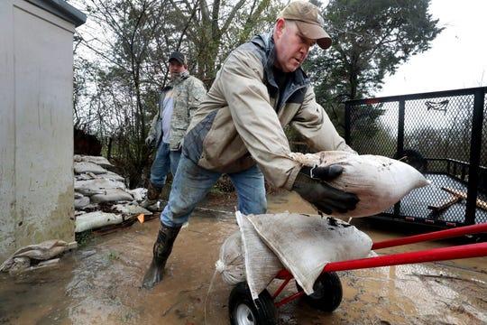 Daniel Kellum Jr. moves sandbags with his son Andrew after overnight flooding Thursday, Feb. 6, 2020 outside Murfreesboro, Tenn.