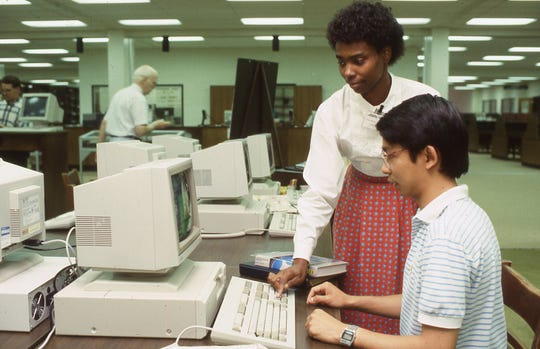 Library employee Melanie Thomas assists a student in the Todd Library's CD-ROM center in this 1987 file photo.