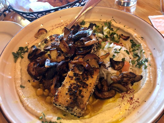"""The Everything Vegan"""" hummus bowl is made with sautéed mushrooms and strips of tofu crusted with """"everything"""" seasoning."""