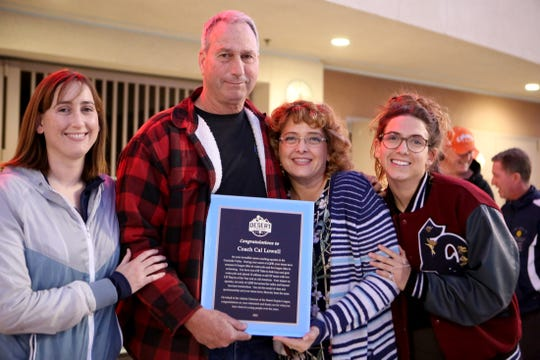 Coach Cal Lowell holds a CIF plaque in recognition of his years as an aquatics coach while being photographed with his wife Michelle and daughters Hannah and Virginia prior to the DEL championship game in La Quinta, Calif., on Wednesday, February 5, 2020.
