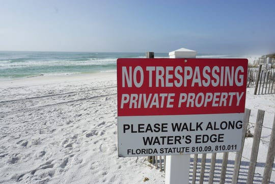 No trespassing signs in Walton County direct beachgoers to walk along the water's edge.