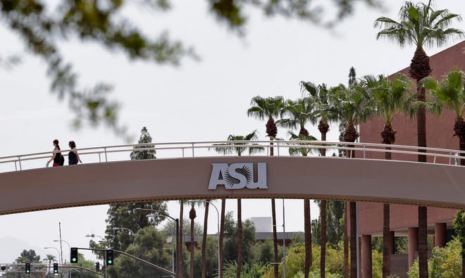 In this July 25, 2018, file photo, pedestrians cross over University Avenue on the campus of Arizona State University in Tempe.