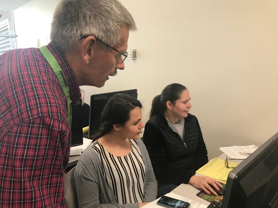 Dennis Molnar and Claudia Aguilar help Elmira Kamyab, center, file her income-tax return for free.
