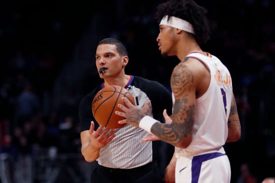 Referee Nate Green hands the ball to Phoenix Suns forward Kelly Oubre Jr. during the first half of an NBA basketball game against the between the Detroit Pistons, Wednesday, Feb. 5, 2020, in Detroit. (AP Photo/Carlos Osorio)