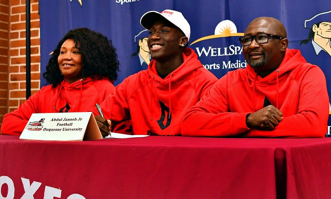 Abdul Janneh Jr., center, is flanked by his parents, Claudia, left, and Janneh Abdul Sr.,  as they pose for photos during signing day at New Oxford High School in New Oxford, Wednesday, Feb. 5, 2020. The senior will be playing football for Duquesne  University. Dawn J. Sagert photo