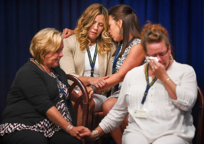FILE - In this Tuesday, Aug. 14, 2018 file photo, those affected by clergy sexual abuse comfort each other as Attorney General Josh Shapiro speaks at a news conference in the State Capitol Building in Harrisburg, Pa. The landmark grand jury report looked at how abuse allegations were handled in six dioceses. (Steve Mellon/Post-Gazette via AP)