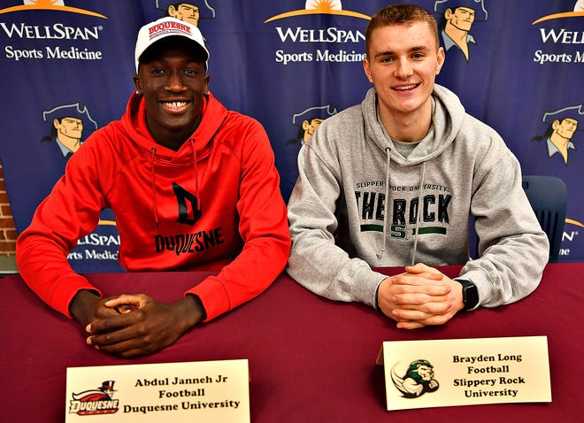 Abdul Janneh Jr., left, and Brayden Long are shown during signing day at New Oxford High School in February of 2020. The seniors chose to play football for Duquesne and Slippery Rock universities, respectively. Athletes in the Class of 2021, during the COVID-19 era, found many more challenges attracting offers from college coaches. Dawn J. Sagert photo