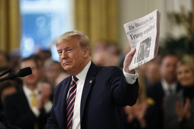 """President Donald Trump holds up a newspaper with the headline that reads """"Trump acquitted"""" as he speaks in the East Room of the White House in Washington, Thursday, Feb. 6, 2020. (AP Photo/Patrick Semansky)"""