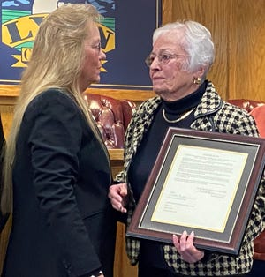 Lyon County Commission Chairwoman Vida Keller (left) presents Phyliss hunewill with a resolution in honor of her son and former Commissioner Greg Hunewill, who died in 2019.