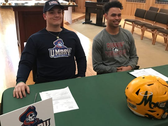 Bishop Manogue seniors Ethan Carson, left, and Curtis Luckadoo, signed to play college football in a ceremony at Bishop Manogue on Wednesday.