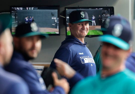 FILE - In this April 12, 2019 file photo, Seattle Mariners manager Scott Servais, center, smiles in the dugout before a baseball game against the Houston Astros in Seattle. Spring training for the Mariners ahead of the 2020 season will feature young players and prospects that could be at the heart of whether the Mariners' rebuild plans ultimately work.