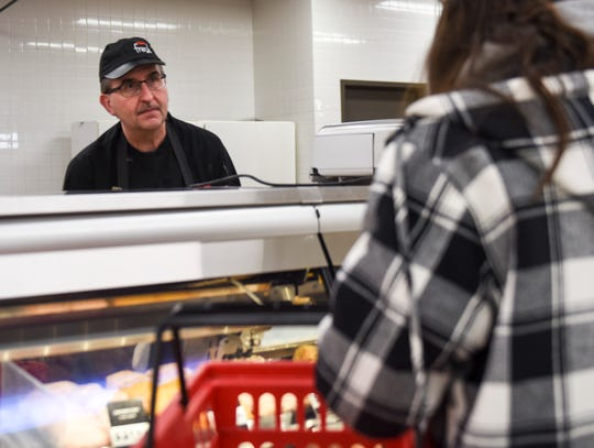 Scott Haisch assists a customer at the meat counter on Thursday, Feb. 6, 2020 at the Hy-Vee on Minnesota Avenue. Hy-Vee recently announced a change in their stores hours and will no longer be open 24 hours.
