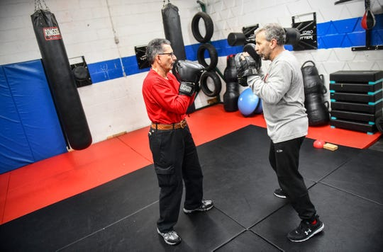 Joe Mehr works with instructor Scott Kelm during a Rock Steady Boxing class Wednesday, Feb. 5, 2020, at Downtown Gym & Fitness in St. Cloud.
