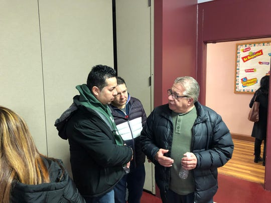 Former Doral Arrowwood worker Guillermo Pinel (right) speaks with two former colleagues following a meeting about getting severance pay after they were laid off on short notice.
