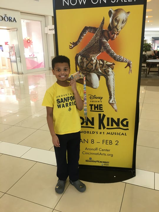 "Newark's Charlie Kahler, 10, poses with a poster for the touring Broadway musical ""The Lion King"" in Ohio recently. He debuted as Young Simba at the end of January at a show in Cincinnati."