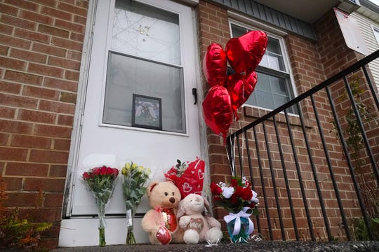 A memorial sits outside an apartment where a woman and two children were found dead Wednesday. A man who was reportedly the woman's husband was found dead miles away.