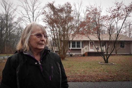 Linda Dyson stands in front her home on Sportsman Road in Carneys Point, New Jersey, where she has lived for over 38 years. Yesterday police found a body hanging in the woods across the street that she could see from the front window of her home. The man was later linked to the deaths of three family members found at Penns Grove Gardens apartments.