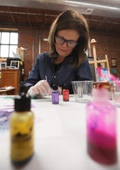 Zanesville multi-media artist Sandy Booth works on a piece in her studio in the Art Loft in downtown Zanesville.