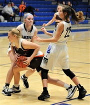 Zanesville's Maddy Winland (left) and Abbi Edwards battle for possession with a Meadowbrook player in Wednesday's game. Zanesville won 54-30.