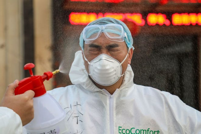 This photo taken on Feb. 3, shows a doctor being disinfected by his colleague at a quarantine zone in Wuhan, the epicenter of the coronavirus outbreak, in China's central Hubei province.