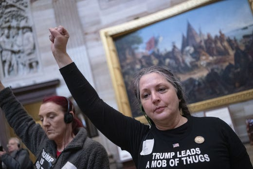 Demonstrators raise their fists in favor of President Donald Trumps removal of office conduct a protest in the Rotunda of the U.S. Capitol.