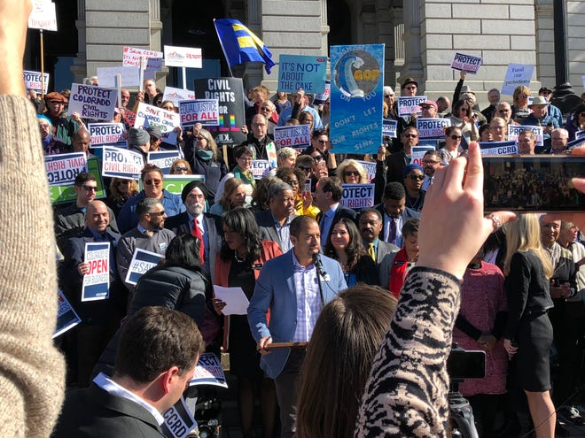 Daniel Ramos of One Colorado, center, speaks at a rally to save the Colorado Civil Rights Division, which was under threat to be de-funded in 2018.