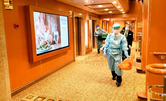 In this Tuesday, Feb. 4, 2020, photo taken by a passenger, medical workers in protective suits walk on the cruise ship Diamond Princess anchored off Yokohama, south of Tokyo.