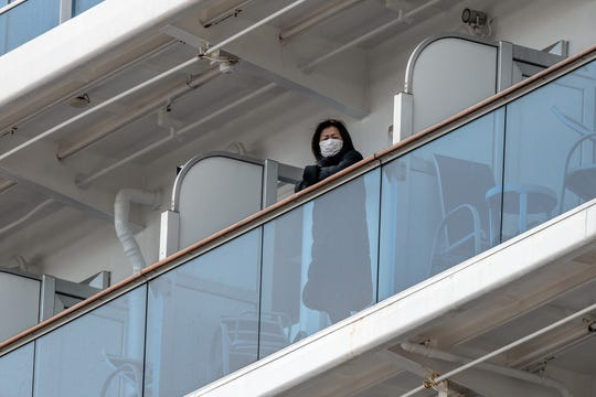A passenger looks out from a balcony of the Diamond Princess cruise ship while it is docked at Daikoku Pier.