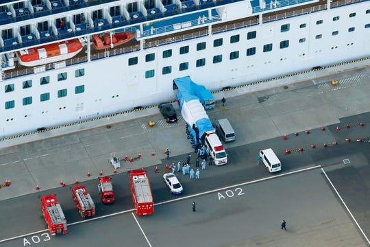 An ambulance waits for passengers to disembark from the cruise ship Diamond Princess anchored at Yokohama Port in Yokohama, south of Tokyo.