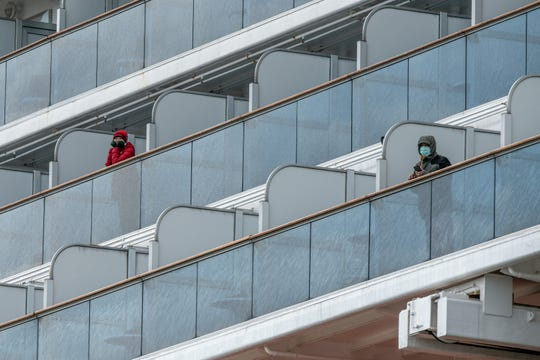 YOKOHAMA, JAPAN - FEBRUARY 06: Passengers look out from a balcony of the Diamond Princess cruise ship while it is docked at Daikoku Pier.