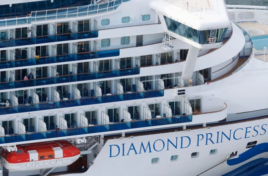 Some passengers are seen on the Diamond Princess as the cruise ship is anchored.