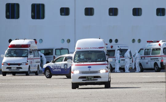 Ambulances wait on the dock near the Diamond Princess cruise ship to transfer passengers who tested positive for the new coronavirus, at the Daikoku Pier Cruise Terminal.