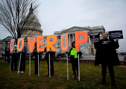 Protesters carry signs outside the Capitol in Washington, DC, on February 5, 2020, after the US Senate acquited the US president in his impeachment trial. The US Senate acquitted President Donald Trump of abuse of power and obstruction of Congress following a historic two-week trial.