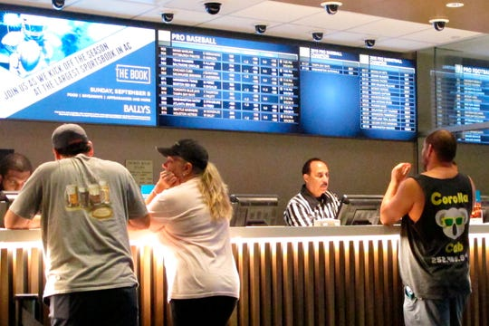In this Sept. 5, 2019 photo, gamblers place sports bets at Bally's casino in Atlantic City, N.J.