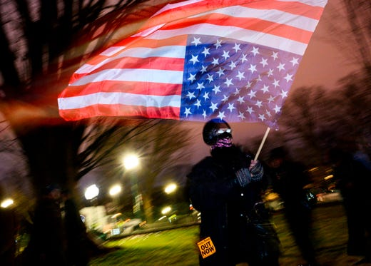A protester waves a US national flag upside down, in a sign of distress, outside the Capitol in Washington, DC.