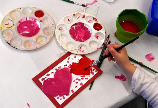 Henley Benham, 4, colors in the hearts she made on a Valentine's Day card.