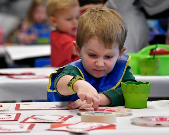 Westin Walders, 5, ensures his finger is well-covered with paint which he was using to create the outlines of a heart on his card Friday. Nearby, his grandmother, Sharron McClellan, ensured the paint didn't travel too far up his arm.