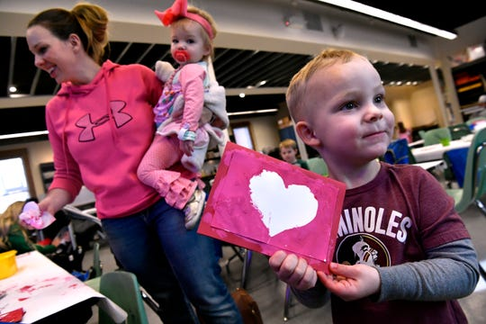 Sam Collier, 4, holds the Valentine's Day card he made Friday as his mother, Hilary, while his 1-year-old sister Katie cleans up in the background. The Grace Museum's February activity at the Tot Spot was making the cards in time for the special day.
