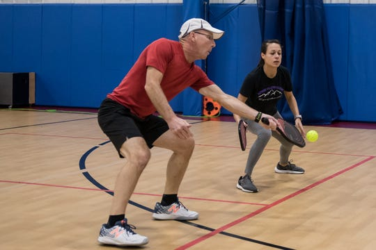 Rick Shrier and Flori Lambos play doubles pickleball in a facility in Hendersonville. Asheville Parks and Recreation is considering a dedicated pickleball court at Recreation Park in East Asheville.