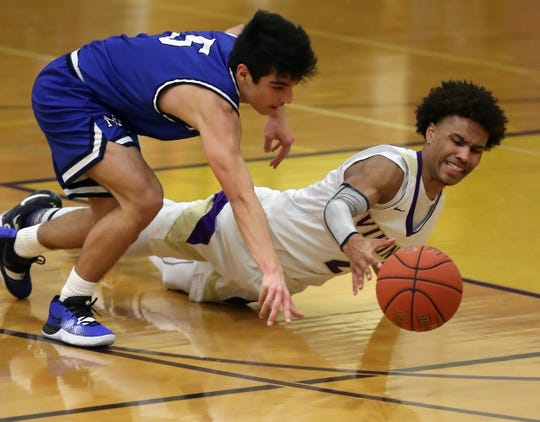 North Kitsap's Kobe McMillian (2) and North Mason's Reid Williams (5) dive for a loose ball during the second half of their game in Poulsbo on Thursday, Feb. 6, 2020.