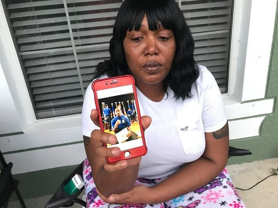 Chemeta Jundon holds cellphone bearing image of her son Franklin Reed III