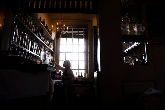 Bartender Kelli Mantell works inside City Tavern in Philadelphia.