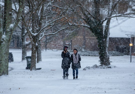 Children walk to a bus stop in Forest Park on Friday. Winton Woods City Schools were not on a delay because of the snow.