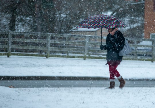 A woman makes her way through the snow along Northland Blvd in Forest Park on Friday morning.