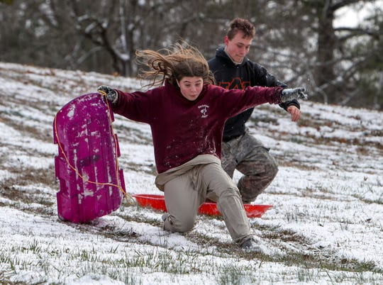 Isabelle Stilwell, 12, slips while walking down the hill as her brother Tyler, 16, back, jumps onto his sled to head down the face at Emerald Hill in Clarksville, Tenn., on Friday, Feb. 7, 2020.