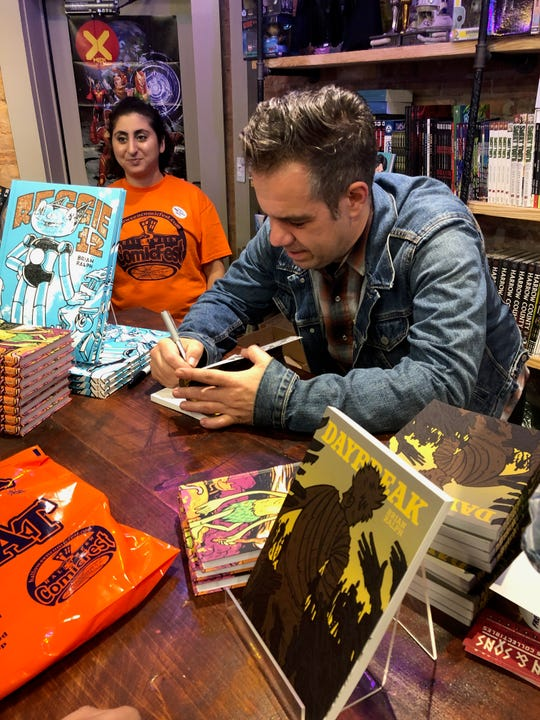 """Brian Ralph, formerly of Metuchen, autographing copies of his graphic novel """"Daybreak,"""" which was recently adapted into a Netflix series."""