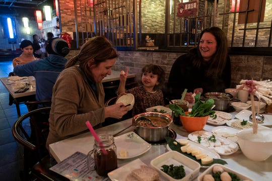 Silke Gischer of Royal Oak, left, Evelyn Jones, 3, center, and her mother Melanie Jones, both of Woodhaven, wait for their hot pot to boil at Lao Pot in Madison Heights, Thursday, Feb. 6, 2020.