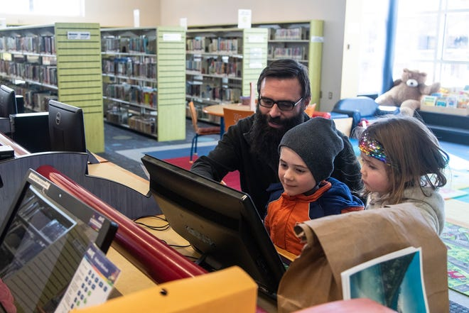 Jeff Giroux watches his son Isaac, 7, and daughter Pearl, 4, play a game on the computer at Ferndale Public Library in Ferndale, Friday, Feb. 7, 2020.