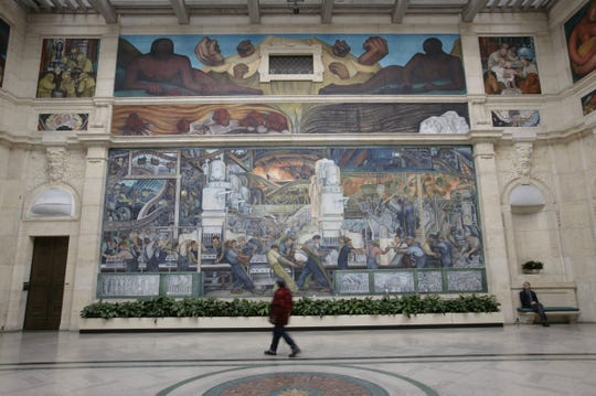 A visitor walks through Rivera Court at the Detroit Institute of Arts, viewing Detroit Industry, painted by Diego Rivera in this file photo.