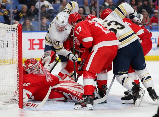 Sabres center Curtis Lazar (27) and Winds defenseman Filip Hronek (17) go after the loose puck as goaltender Jonathan Bernier looks to cover the puck during the second period in Buffalo on Thursday.